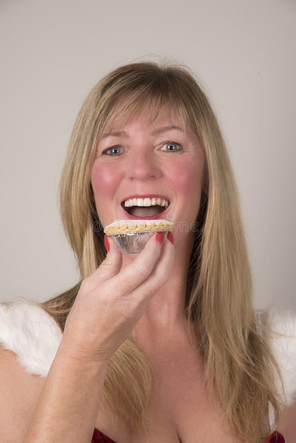 Vrouw die een Mince pastei eten stock foto