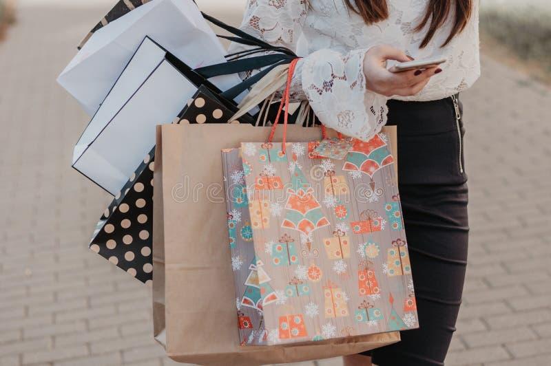 Vrouw die een mobiele telefoon met het winkelen zakken in handen met behulp van royalty-vrije stock afbeelding