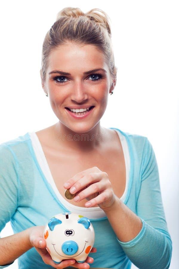 Vrouw die een muntstuk zetten in haar spaarvarken royalty-vrije stock foto