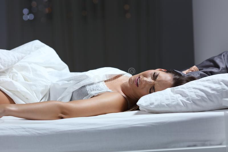 Vrouw die een nachtmerrie in het bed in de nacht hebben royalty-vrije stock afbeelding