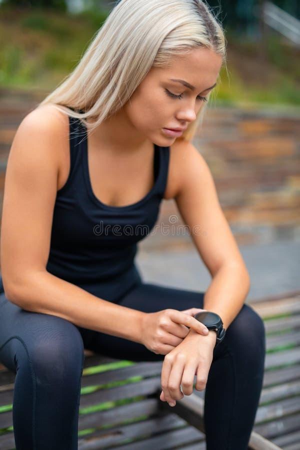 Vrouw die een Onderbreking na Training nemen en Tijd controleren op Smartwat stock foto's