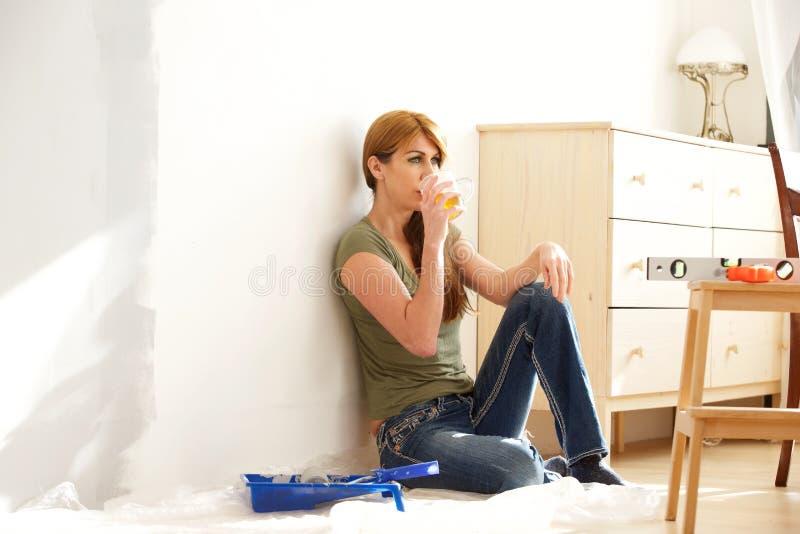 Vrouw die een onderbreking van huisvernieuwing nemen stock foto