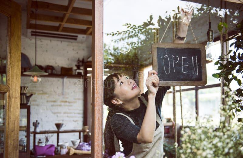 Vrouw die een open teken hangen stock afbeeldingen