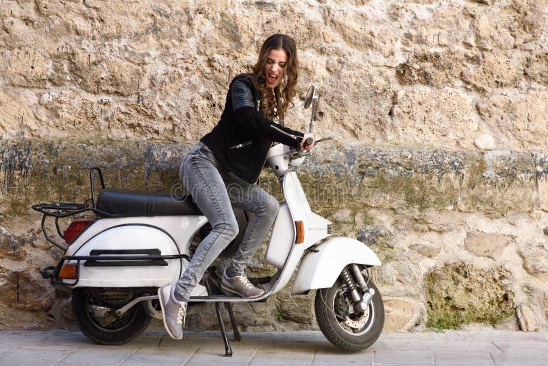 Vrouw die een oude autoped met pedaal lanceren stock afbeelding