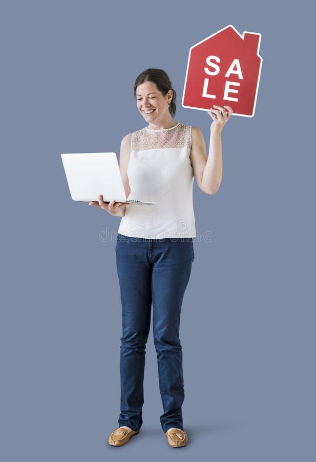 Vrouw die een pictogram van de huisverkoop en laptop houden stock foto