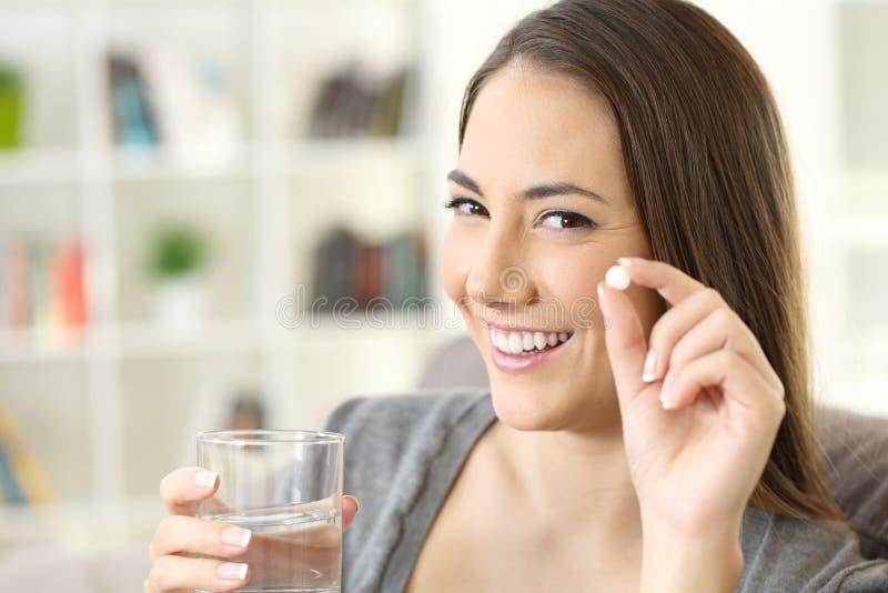 Vrouw die een pil houden bekijkend camera stock foto