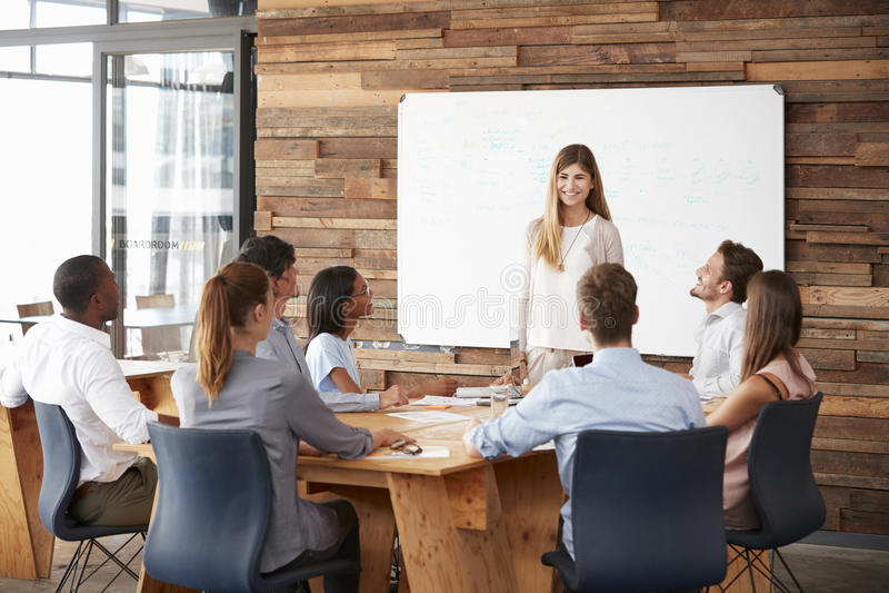Vrouw die een presentatie geven bij whiteboard aan commercieel team stock fotografie