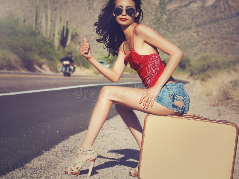 Vrouw die een rit op woestijnweg hitching royalty-vrije stock afbeeldingen