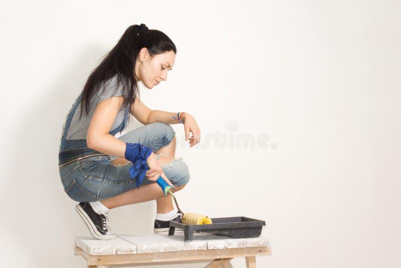 Vrouw die een rol met behulp van om een muur te schilderen royalty-vrije stock afbeeldingen
