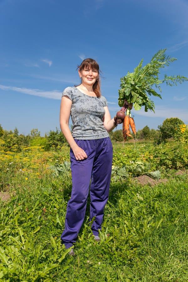 Vrouw die een schoof van groenten in de hand houden stock afbeelding
