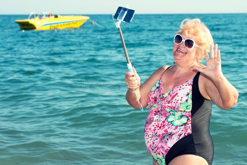 Vrouw die een selfie op een mobiele telefoon op het strand nemen De vakantie van de zomer royalty-vrije stock fotografie