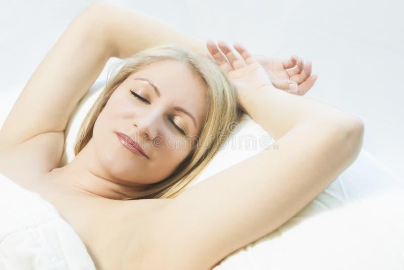 Vrouw die een slaap met een glimlach op haar gezicht heeft royalty-vrije stock afbeelding