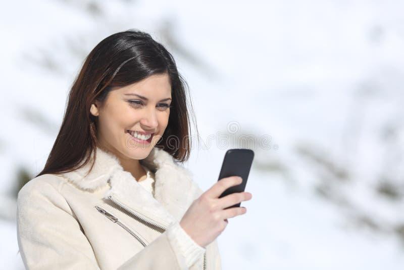 Vrouw die een slimme telefoon op de wintervakantie met behulp van stock afbeelding