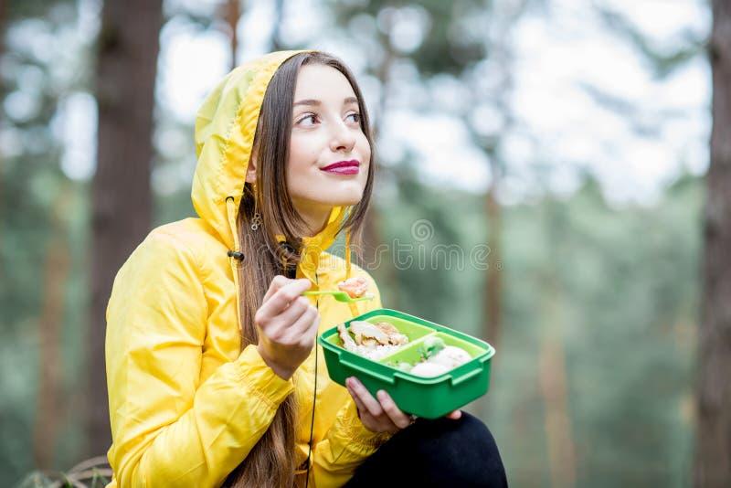 Vrouw die een snack in het bos hebben stock afbeeldingen