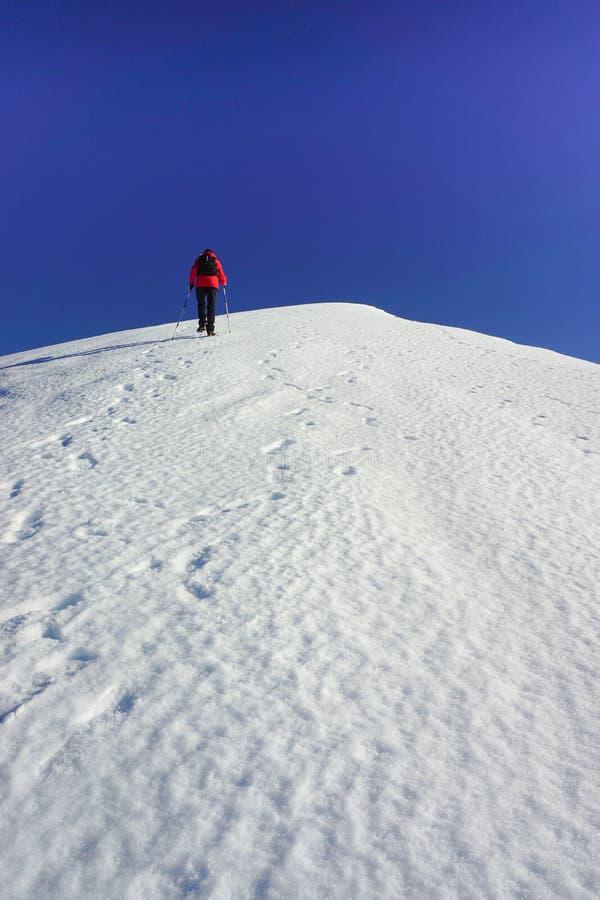 Vrouw die een sneeuwhelling beklimmen stock foto