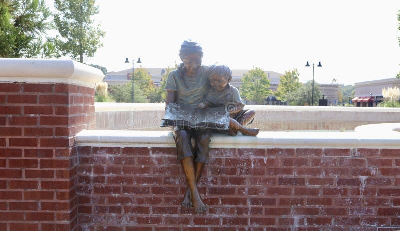 Vrouw die een Standbeeld van het Boekbrons lezen stock foto's