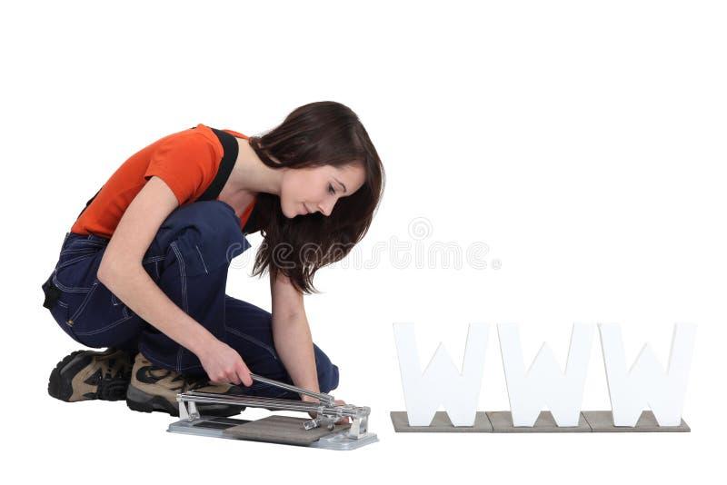 Vrouw die een tegelsnijder met behulp van stock afbeelding