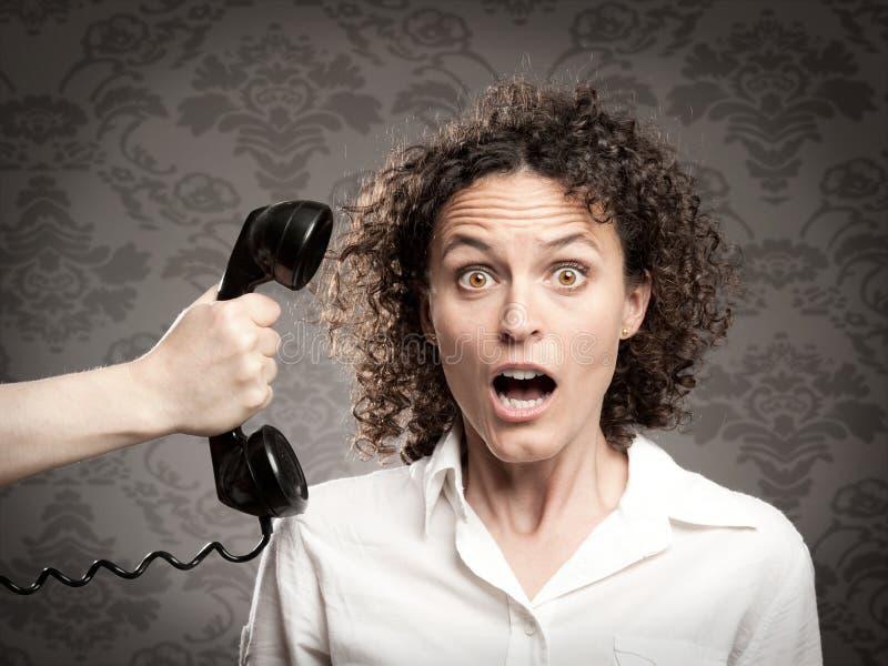 Vrouw die een telefoongesprek bijwoont stock foto's