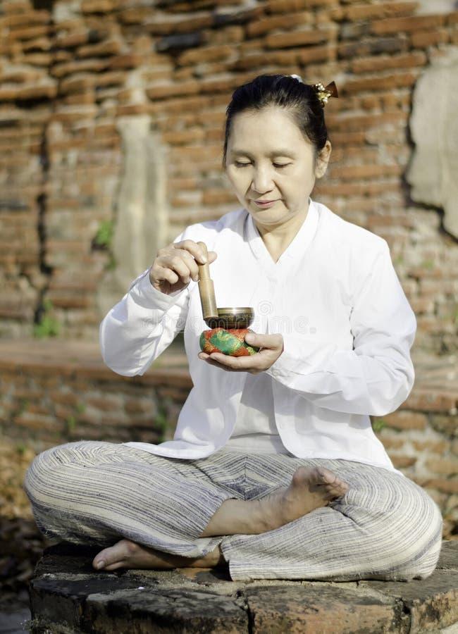 Vrouw die een tibetan kom spelen, die traditioneel aan hulpmeditati wordt gebruikt stock afbeelding