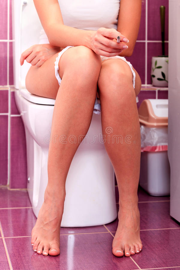 Vrouw die in een toiletruimte roken royalty-vrije stock afbeeldingen