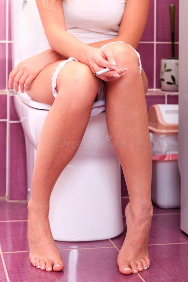 Vrouw die in een toiletruimte roken royalty-vrije stock afbeelding