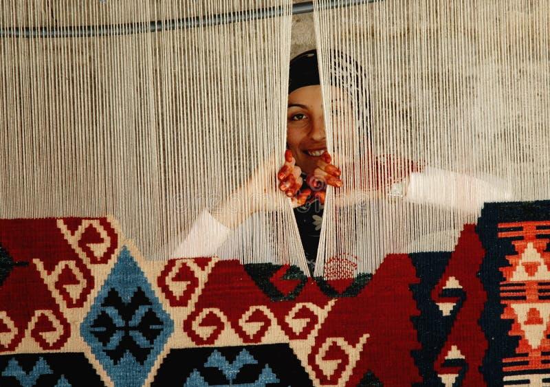 Vrouw die een traditioneel Turks tapijt weeft stock afbeelding