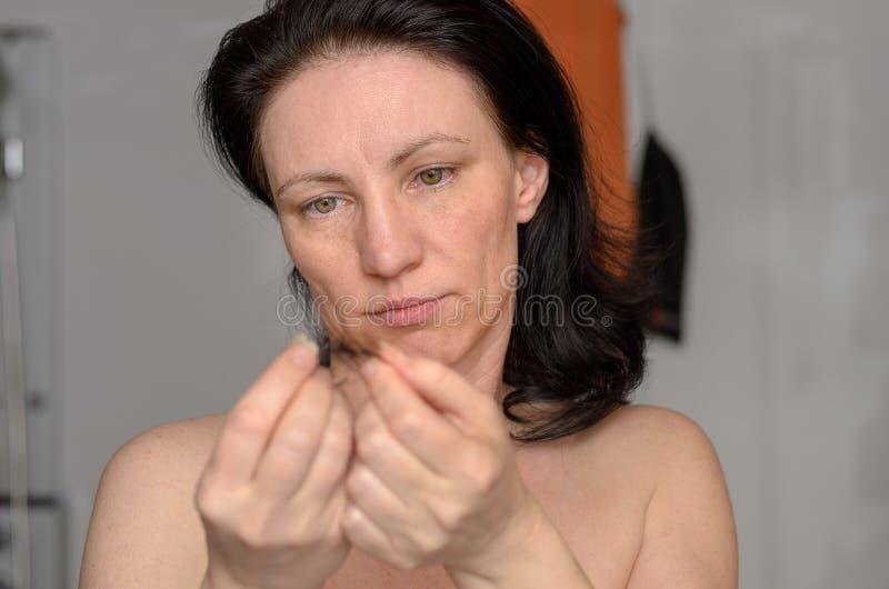 Vrouw die een verwarring van los bruin haar houden royalty-vrije stock fotografie