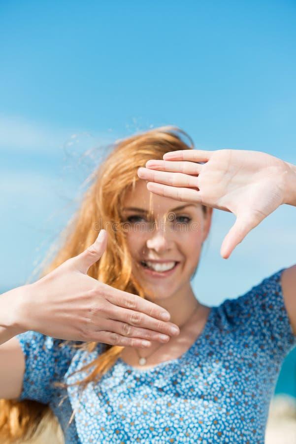 Vrouw die een vingerkader maakt stock fotografie