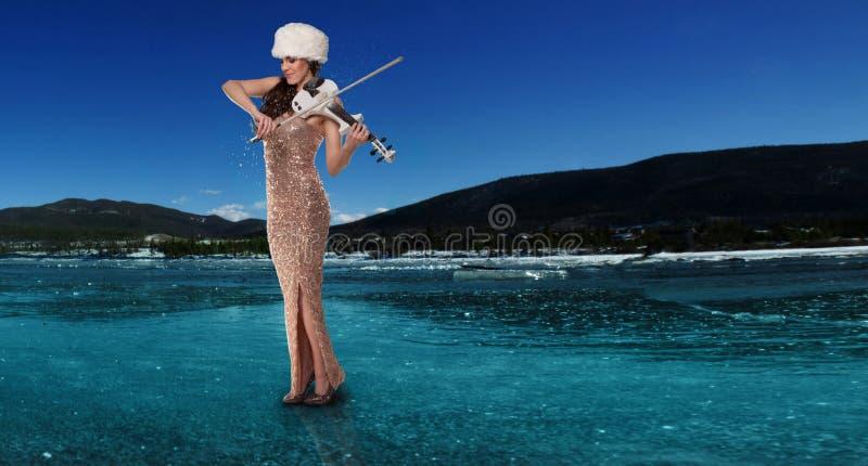 Vrouw die een viool op een bevroren meer spelen stock foto's