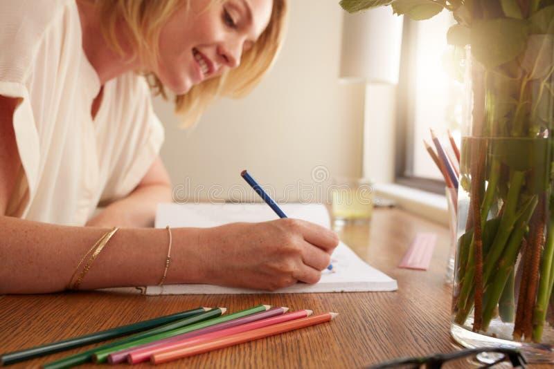Vrouw die een volwassen kleurend boek met potloden kleuren stock afbeeldingen