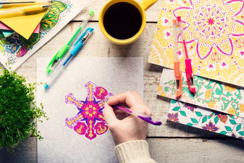 Vrouw die een volwassen kleurend boek, nieuwe spannings verlichtende tendens kleuren stock afbeeldingen