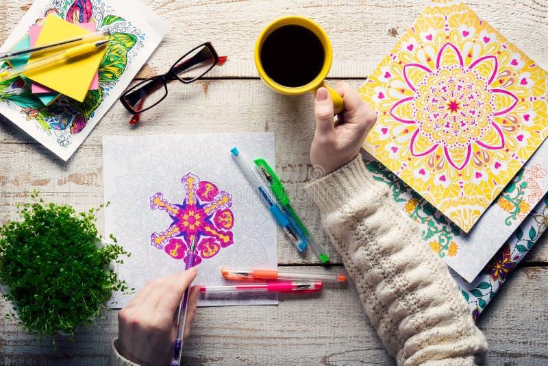 Vrouw die een volwassen kleurend boek, nieuwe spannings verlichtende tendens, mindfulnessconcept kleuren royalty-vrije stock foto's