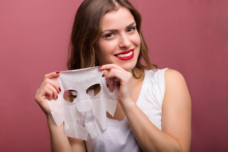 Vrouw die een weefselmasker toepassen stock foto
