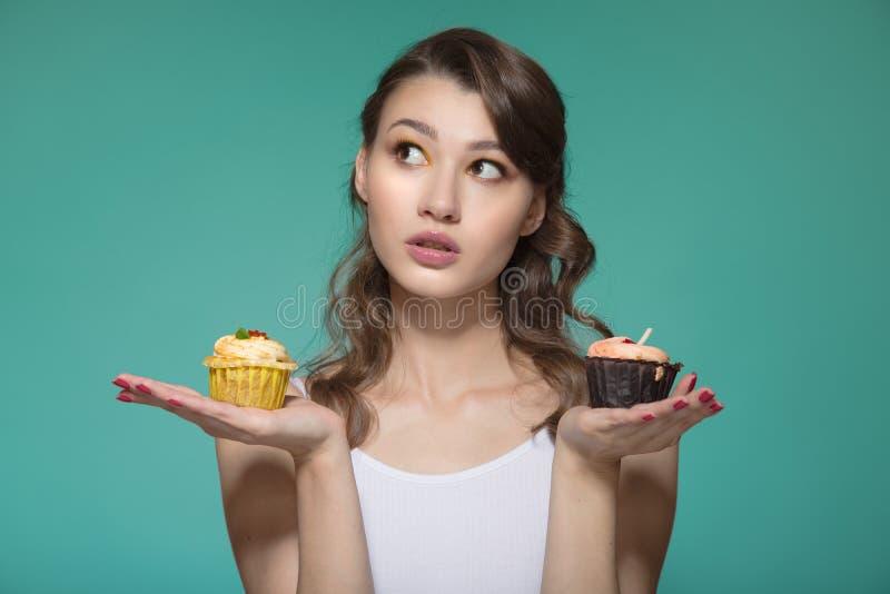 Vrouw die een zoet dessert houden Kies tussen twee cakes Turkooise achtergrond stock afbeeldingen