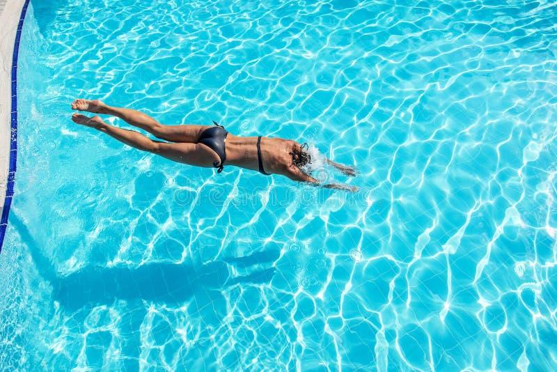 Vrouw die in een zwembad springen royalty-vrije stock foto's