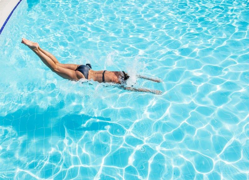 Vrouw die in een zwembad springen royalty-vrije stock foto