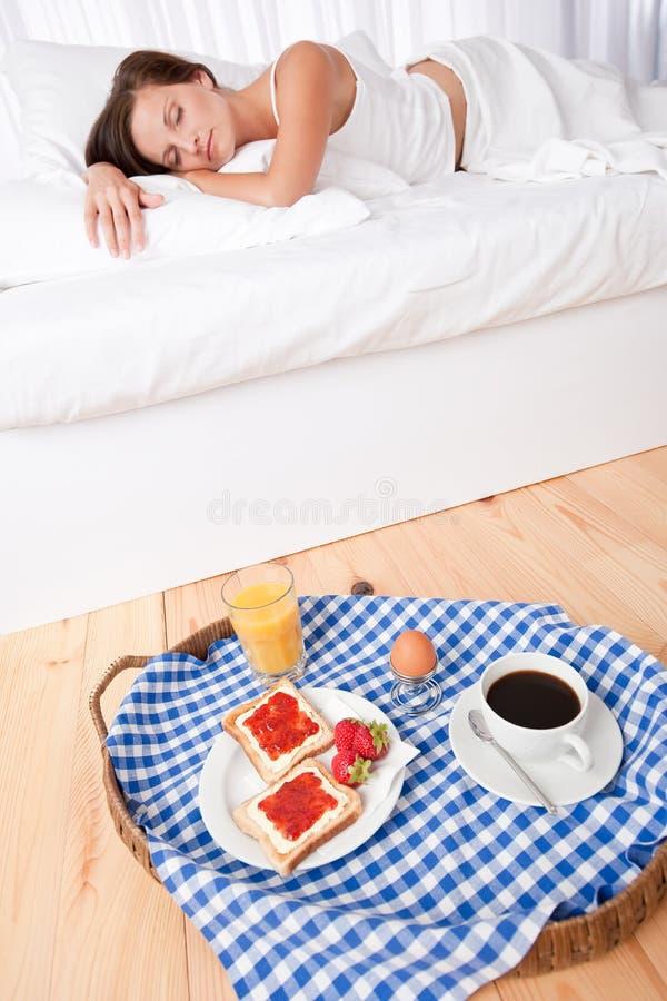 Vrouw die eigengemaakt ontbijt heeft dat in bed ligt stock afbeelding