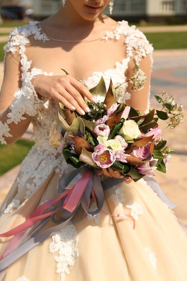 Vrouw die in elegante huwelijkskleding luxueus huwelijk houden bouque royalty-vrije stock foto