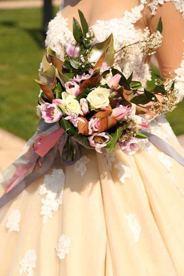 Vrouw die in elegante huwelijkskleding luxueus huwelijk houden bouque stock foto