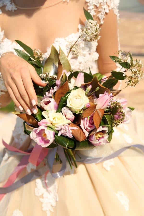 Vrouw die in elegante huwelijkskleding luxueus huwelijk houden bouque stock afbeelding