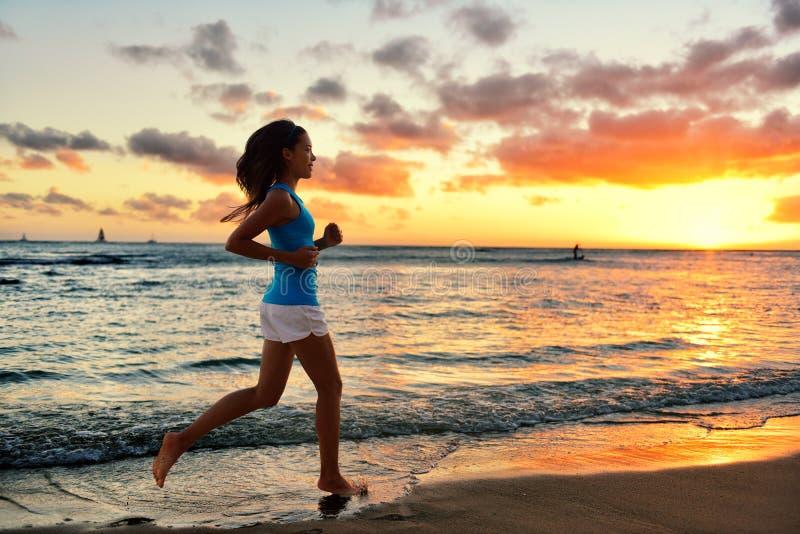 Vrouw die en de zonsopgang van het opleidingsstrand in werking stellen aanstoten stock afbeeldingen