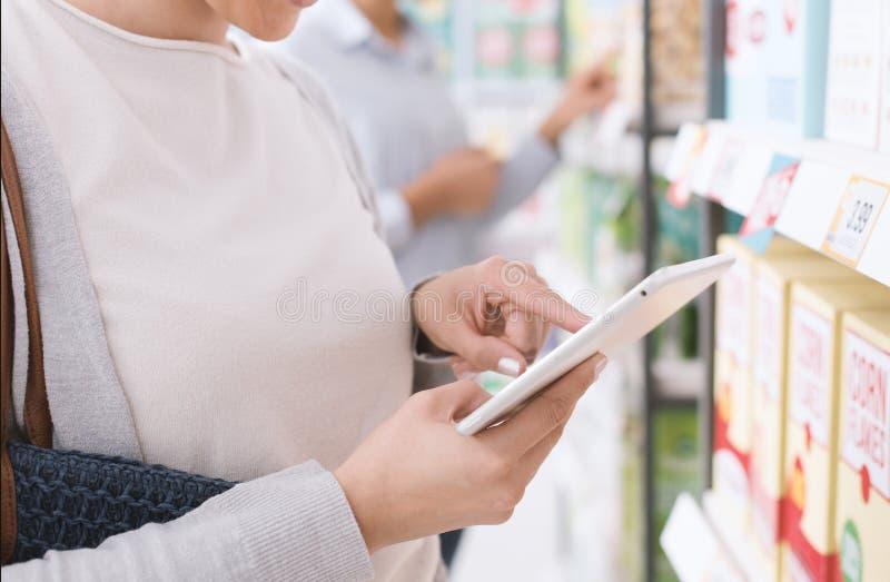 Vrouw die en een tablet gebruiken winkelen stock foto's