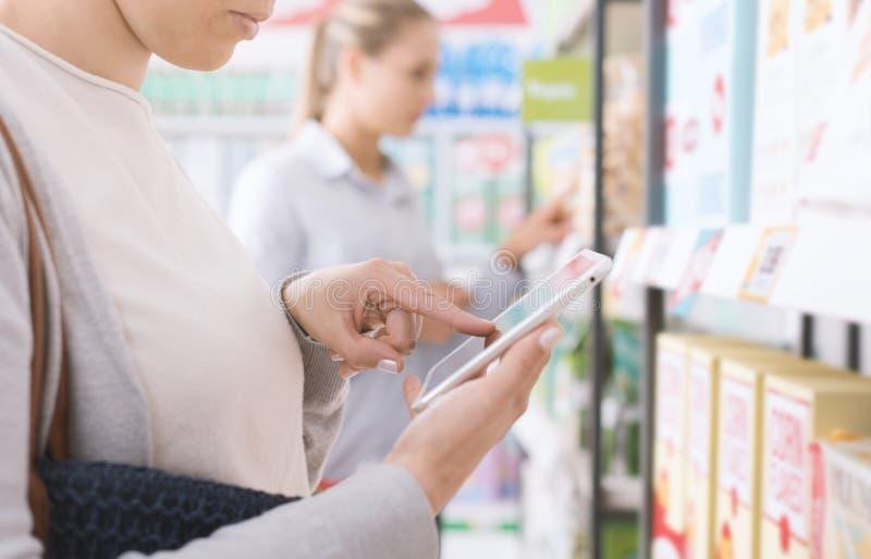 Vrouw die en een tablet gebruiken winkelen stock afbeeldingen