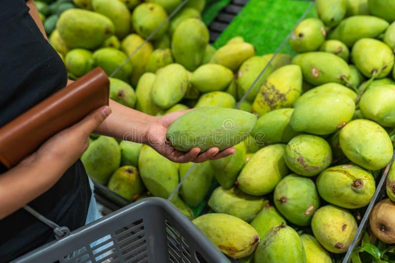 Vrouw die en groene mango kopen plukken bij fruitmarkt royalty-vrije stock fotografie