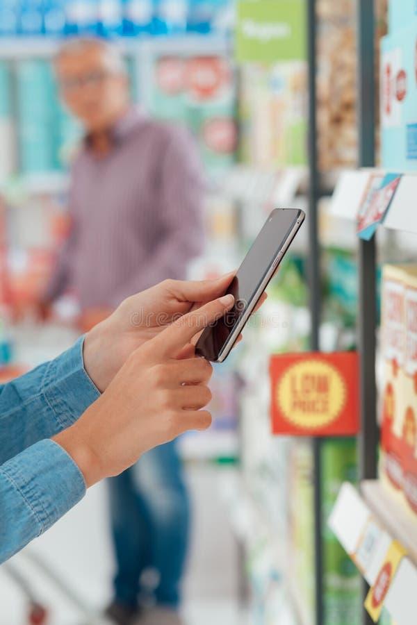 Vrouw die en haar telefoon met behulp van winkelen stock fotografie