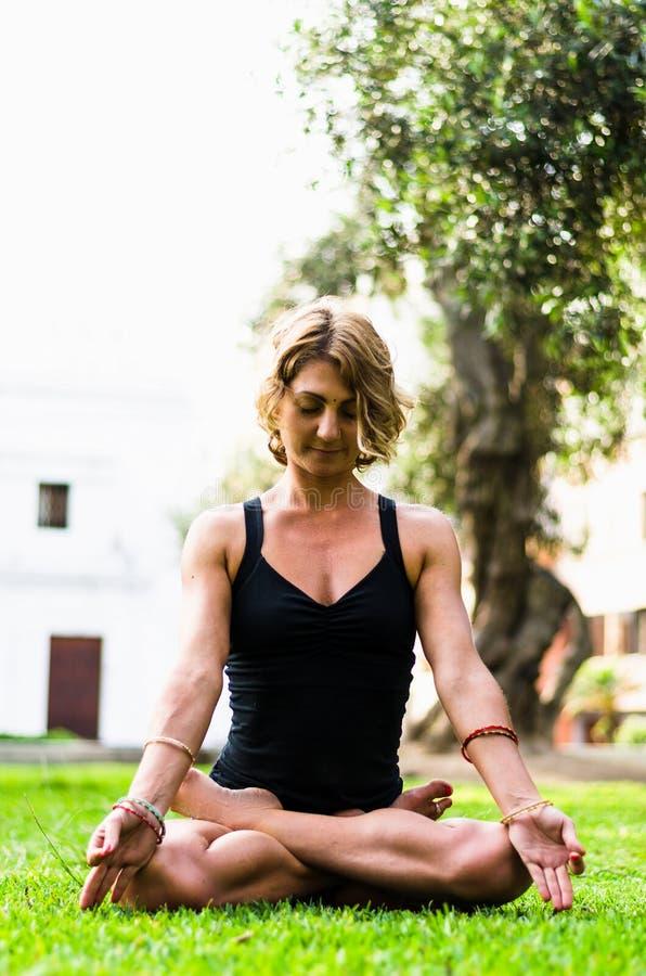 Vrouw die en het Praktizeren Yoga, Padmasana mediteren Meditatie op Sunny Autumn Day At Park Training Openlucht royalty-vrije stock afbeelding