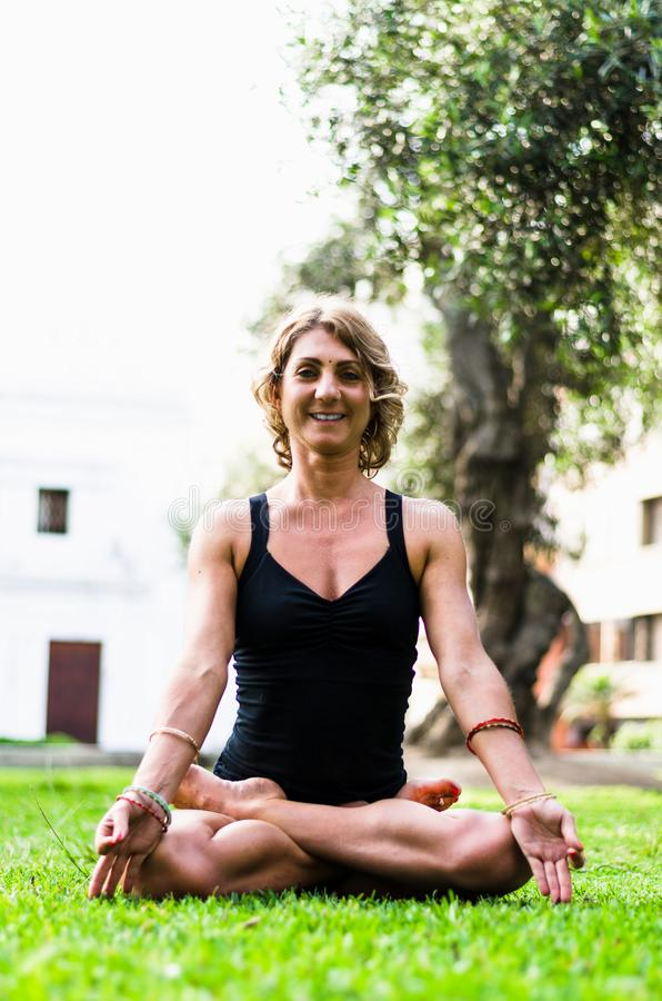 Vrouw die en het Praktizeren Yoga, Padmasana mediteren Meditatie op Sunny Autumn Day At Park Training Openlucht stock foto's