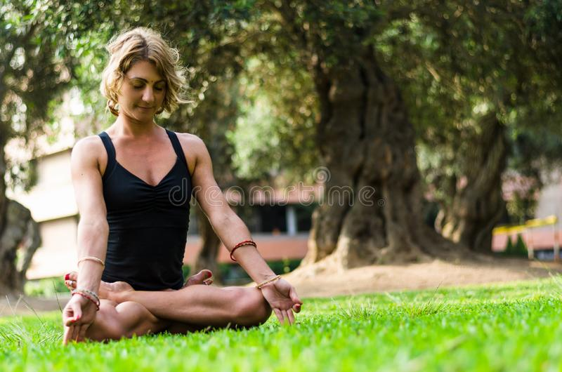 Vrouw die en het Praktizeren Yoga, Padmasana mediteren Meditatie op Sunny Autumn Day At Park Training Openlucht stock foto