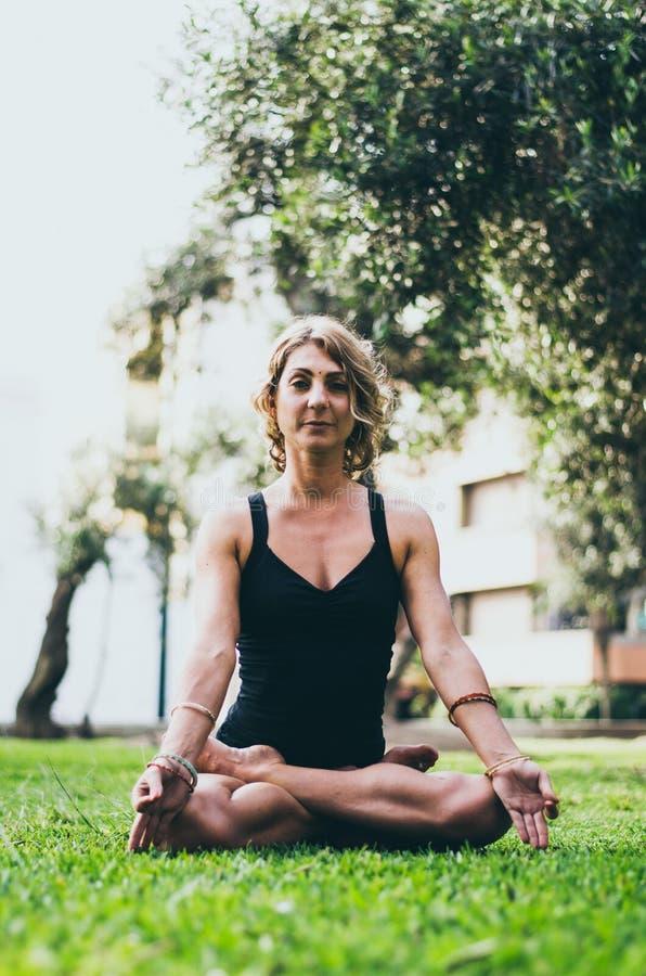 Vrouw die en het Praktizeren Yoga, Padmasana mediteren Meditatie op Sunny Autumn Day At Park Training Openlucht stock fotografie