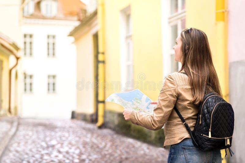 Vrouw die en kaart in de stadsstraat lopen houden royalty-vrije stock afbeeldingen